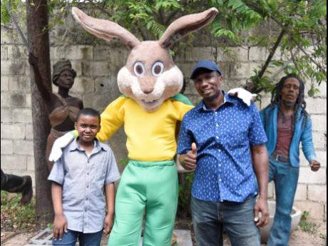 Scheed Cole (right), sculptor of Mr Protector, and Richard Small, student of Bamboo Primary and Junior High School in St Ann who won the Child Protection Mascot competition in 2019, flank the mascot that will be used in the promotion of child safety and de