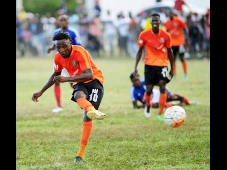 Tivoli Gardens' Jermaine Johnson shoots at goal during a Jamaica Premier League match against Portmore United at the Edward Seaga Sports Complex.