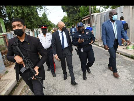 Major General Antony Anderson (centre), commissioner of police, chats with Superintendent Tommie-Lee Chambers, (second right) and Fitz Bailey, (right) deputy commissioner of police in charge of crime during a tour in Flanklyn Town yesterday after an attack