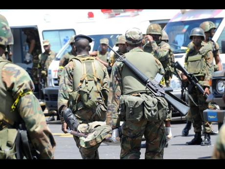 Soldiers carry a colleague injured in the gun battle at Tivoli Gardens in this May 2010 photograph. The incursion which took place over May 24–25, left at least 73 civilians dead and 35 wounded. Four security personnel, from JDF and JCF were also killed.