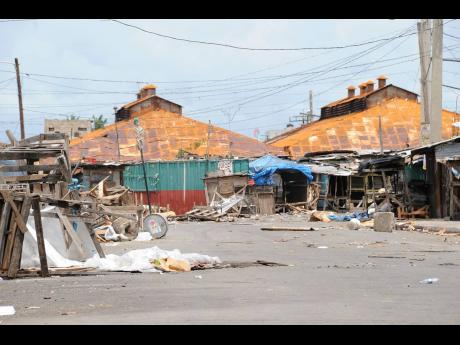 In this file photo taken on May 26, 2010, streets in front of Coronation Market, downtown Kingston, are strewn with debris after the military operation in Tivoli Gardens.