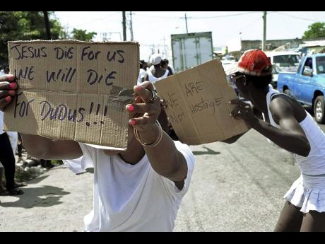 In this May 20, 2010 photo, demonstrators display pieces of cardboard with messages in support of Christopher 'Dudus' Coke during a march in Kingston.