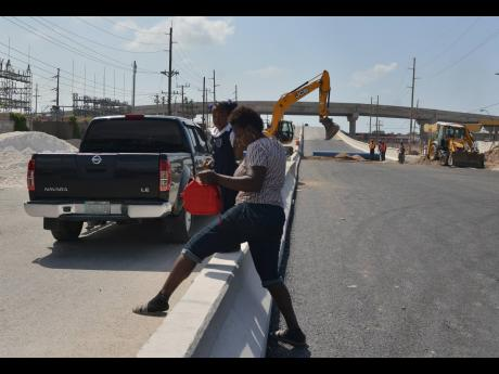 In this file photo, Sophia Bogle and her child negotiate a median on Spanish Town Road, in the vicinity of Majesty Gardens. Experts say that building these high medians, Jersey barriers, is a mistake and contrary to best practices in the world.