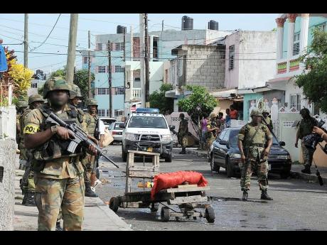 In this May 27, 2010 Gleaner photo, members of the security forces on patrol in Tivoli Gardens in the aftermath of the May 10, 2010 operation.