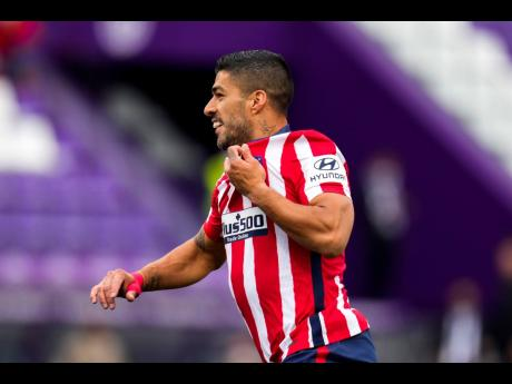 Atletico Madrid's Luis Suarez celebrates after scoring his side's second goal during the Spanish La Liga match between Atletico Madrid and Valladolid at the Jose Zorrilla stadium in Valladolid, Spain, yesterday. Atletico won 2-1 to win the Spanish LaL