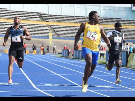 Sachin Dennis (centre) wins his heat in the men's 100m ahead of Kenroy Anderson (left) and Javoy Tucker (right) during the JOA/JAAA Olympic Destiny  Meet at the National Stadium yesterday. Dennis clocked a personal best 10.15 seconds to finish as the fas
