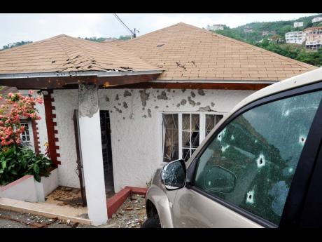 The bullet-riddled house and vehicle at the Kirkland Heights home of Keith Clarke after the May 2010 operation in which he was killed by members of the security forces.