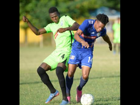 Mount Pleasant's Suelare McCalla (right) jostles for possession of the ball with Molynes United's Sergeni Frankson at the Constant Spring Sports Complex in their Red Stripe Premier League encounter on Sunday, December 15, 2019.