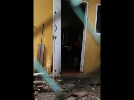 A broken door bears witness to a family dispute which turned deadly in Lionel Town, Clarendon, yesterday. Alrick Williams, who reportedly attacked his brother, was shot dead.