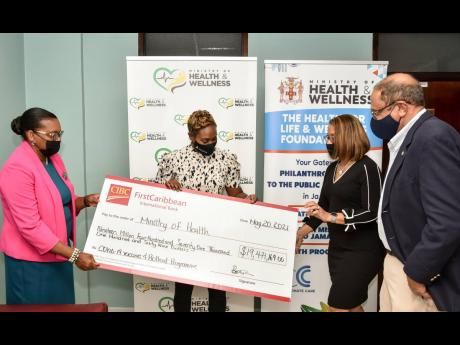 CIBC FirstCaribbean's Human Resources Manager Jerome Griffith (left) and Alison Rattray, corporate secretary and legal counsel (second right), present the bank's cheque for $19 million towards the purchase and roll-out of COVID-19 vaccines in Jamaica t