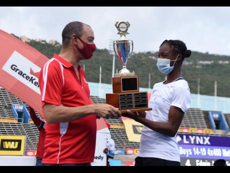 The captain of the Edwin Allen High School girls track and field team, Ackelia Smith (right), collects the championship trophy from Group CEO at GraceKennedy, Don Wehby after winning their seventh title at the ISSA/GraceKennedy Boys and Girls' Athletics