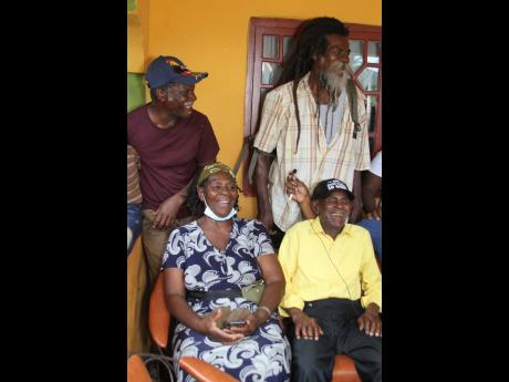 Centenarian William Jennings (sitting right) of  Rock River, Clarendon shares a light moment with three of his children Veda (sitting), standing are: Castel, and  Earl during a function held at his home on Saturday to celebrate his 100th birthday.