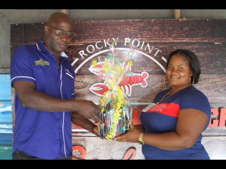 David Dixon, trade development officer, Rum Bar, the main sponsor of 'Pasta Wednesdays' presents a gift to Tanoy Dawkins at White Sands Beach Seafood Restaurant in Rocky Point, Clarendon.