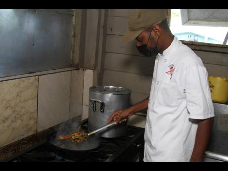 White Sands Beach Seafood Restaurant's Chef Yakini Scott prepares a special dish of buttered crab.