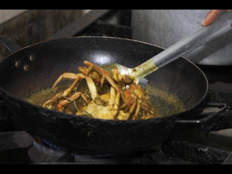 Chef Yakini Scott stirs the buttered crabs.