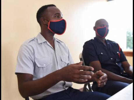 Firefighter Dennis Taylor (left) and Otis Rowe, assistant superintedent in charge of St Catherine speak about the rescue of a man who was trapped in a 55-ft deep hole in St Catherine.