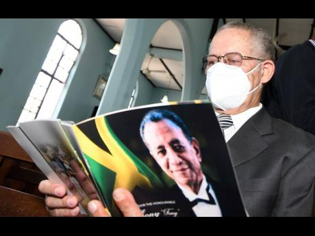 Former Prime Minister Bruce Golding looks at the programme for the service of the late Ambassador Anthony Johnson, inside Kingston College's (KC) St Augustine's Chapel on North Street in Kingston. A KC old boy, Johnson attended the school in the 1950s.