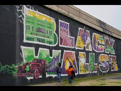 Javohn Perry, left, of Seattle, and her cousin, Danielle Johnson, right, of Beggs, Oklahoma, walk past the Black Wall Street mural in Tulsa, Okla. The original Black Wall Street vaporised a hundred years ago, when a murderous white mob laid waste to what