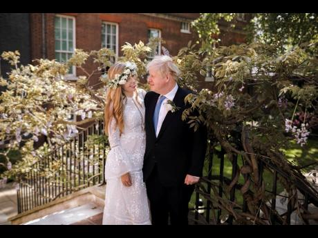 In this image released on Sunday, Britain's Prime Minister Boris Johnson and Carrie Johnson pose together for a photo in the garden of 10 Downing Street after their wedding on Saturday. Boris Johnson and his fiancée Carrie Symonds are newlyweds, according