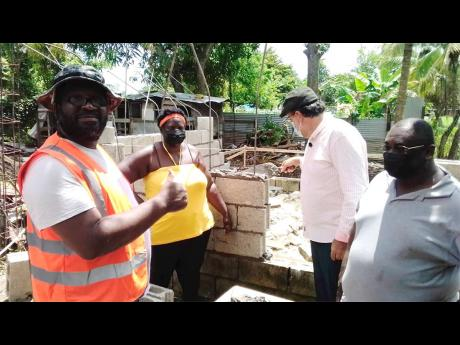 President of the People's National Party, Mark Golding (right), speaks with Davian Hopwood, recipient of an under-construction home in Petersfield, Westmoreland, at a ceremony on Saturday. Also in the photo are councillor for the Petersfield Division, Pa