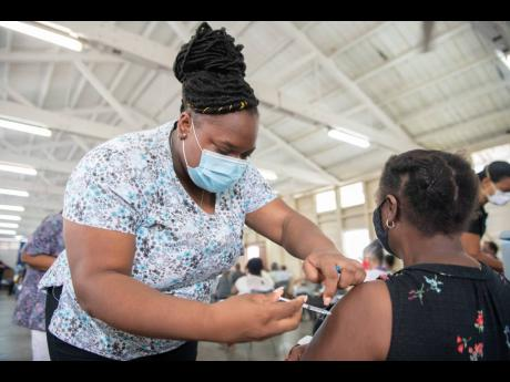 Jescinth Williams receives her COVID-19 jab from registered nurse Yanique Williams at the Mona Ageing and Wellness Centre during the vaccination blitz on Sunday, April 11.