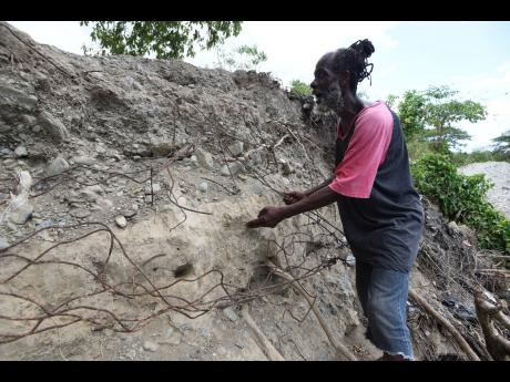 Patrick Roberts, resident of Riverside Drive in Seaforth, St Thomas, shows what is left of the gabion basket that is used to prevent the Negro River from overflowing its banks.