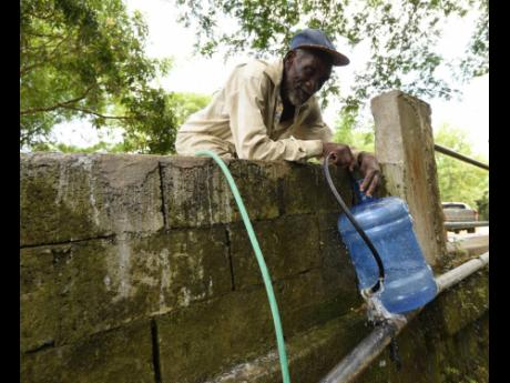 Anthony Roberts catches water from a pipeline in Danvers Pen, St Thomas. The community is one of many in the parish that are prone to flooding.