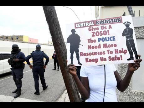 Policemen patrol the intersection of East and Beeston streets in Kingston where a small band of protesters gathered on Tuesday.