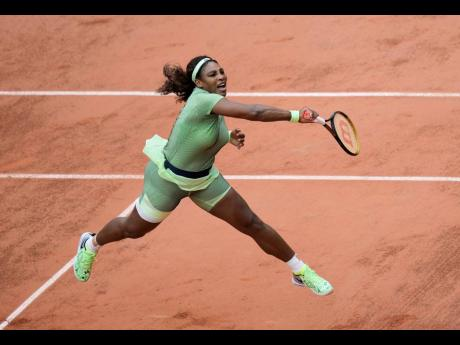 Serena Williams serves to Romania's Mihaela Buzarnescu during their second round match on day four of the French Open tennis tournament at Roland Garros in Paris, France, yesterday.