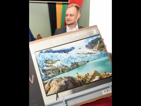 Managing Director of Medimpex West Indies Lukasz Kowalczyk hands over a television set  as a donation to the Kingston Public Hospital in 2020.