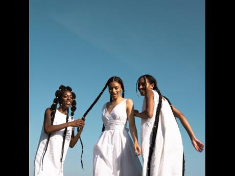 From left: Aalyiah Heath, Sofia Coupellier and Chloe Etienne having a little fun in the field in a photograph for Rebecca Rowe's capstone project.