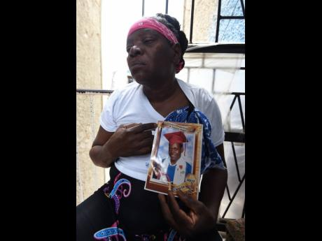 Barbara Richards mourns as she holds a picture of her son, Shedaine Richards, who was fatally shot by gunmen along Rum Lane in the Kingston Central Police Division while on his way home from work on Wednesday night.