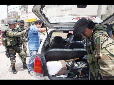 In this 2006 file photo Colombian soldiers are search a car, as part of increased security measures as the military and police prepare for the inauguration of President Uribe in Medellin. The city, once rated as most violent has been working toward buildi