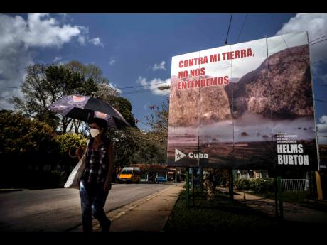 """A woman walks past an anti-embargo sign that reads in Spanish: """"Against my land, we don't understand each other"""", in Viñales, Cuba, on March 1, 2021."""