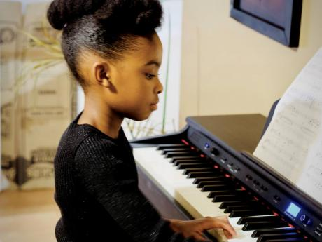 The sixth-grader is being taught to play the piano and other instruments.