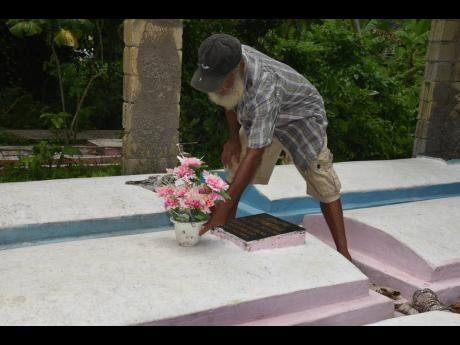 Seventy-three-year-old Marvin Bloomfield rearranging the flowers on the grave of his late wife in the community of Logwood in Hanover last week.