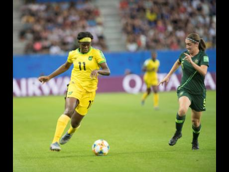 Khadija Shaw (left) dribbles to goal, chased by Australia's defender Karly Roestbakken in  the Jamaica vs Australia fixture of the FIFA Women's World Cup 2019 at Stade des Alpes in Grenoble, France, on Tuesday June 18, 2019.