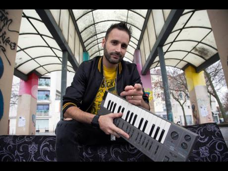 French beatmaker Manudigital poses with another one of his instruments, a model of the Yamaha keyboards.