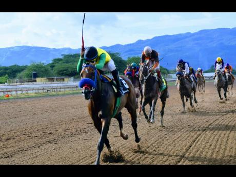 Father Patrick, ridden by Oshane Nugent, takes the Lady Geeta Trophy at Caymanas Park yesterday.