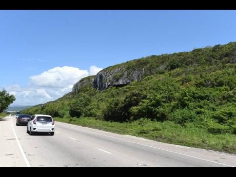 Motorists drive by a section of the limestone-rich Puerto Bueno Mountains, which have been a source of much contention over the past year.