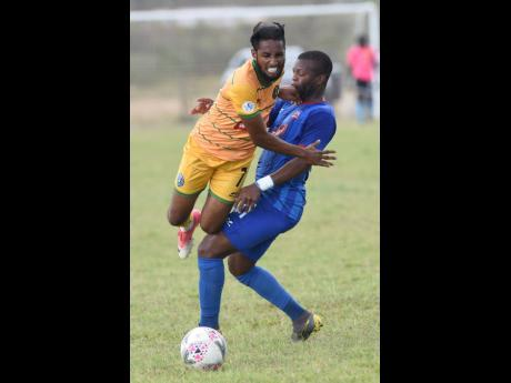 Christopher Randall (left) from Vere United comes under a heavy challenge from Rodave Murray from Dunbeholden United in their Premier League match, which was played at the Wembley Centre of Excellence in Vere, Clarendon, on Sunday, February 16, 2020.