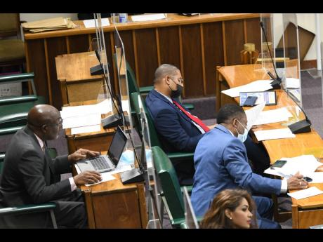 Mikael Phillips (centre), opposition member of parliament for Manchester North West, participates in a sitting  of the House of Representatives on Tuesday. Under-fire Westmoreland Central MP George Wright sat to the left of Phillips briefly on Tuesday, cut