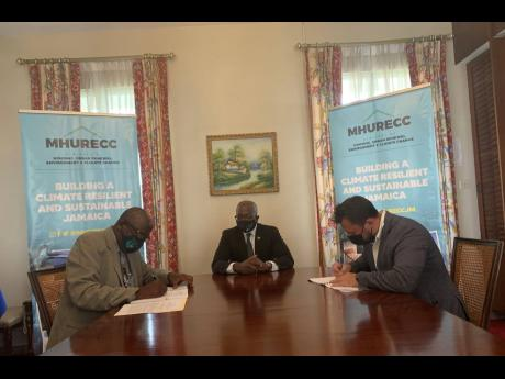 Permanent Secretary in the Ministry of Housing, Urban Renewal, Environment and Climate Change, Alwyn Hales (left) and Isratech's Deputy Chief Executive Officer, Benjamin Hodara (right) sign the farmer field schools contract while Minister Pearnel Charles