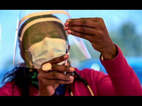 A health worker prepares a dose of the Pfizer coronavirus vaccine at the Orange Farm Clinic near Johannesburg.