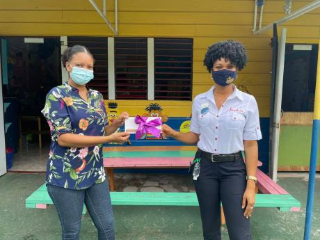 Regional Public Relations Manager for Sandals and Beaches Negril Jervene Simpson (right) stopped by the Happy Hearts Early Childhood in Westmoreland to present a special complimentary two-night/three-day stay at a Sandals in Jamaica to teacher Lacania Coll