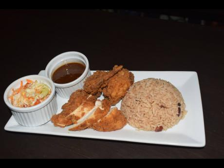 Traditional rice and peas and fry chicken served with raw vegetables. Traditional rice and peas and fry chicken served with raw vegetables.
