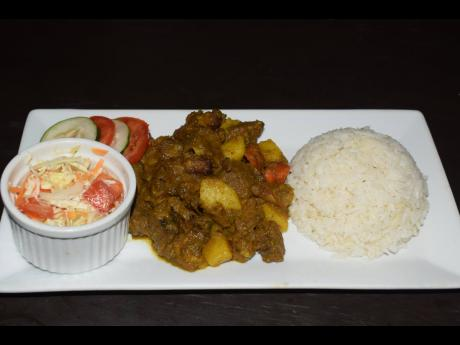 Curried goat served with the customary white rice and serving of raw vegetables.