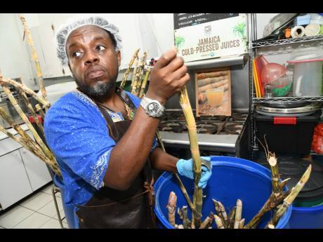 Toussaint Davy, chief juicing officer Jamaica Cold Pressed Juices, prepares to juice sugarcane.