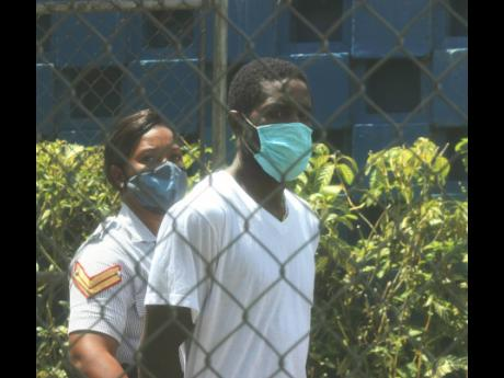 Anthony Bailey is escorted by a policewoman as he was remanded after appearing at the courthouse in Clark's Town, Trelawny, on Wednesday.