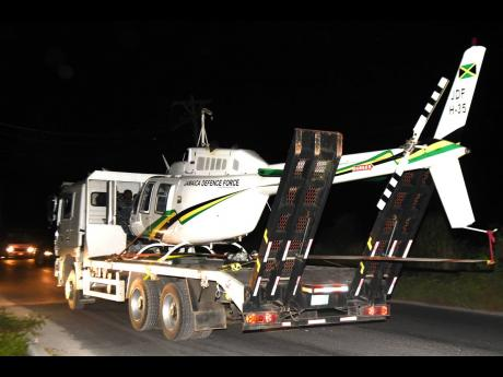 The Jamaica Defence Force helicopter being transported away from the site at which it landed in Dunbeholden, St Catherine, yesterday.